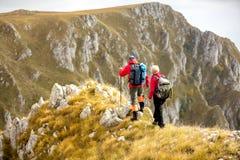 Przygoda, podróż, turystyka, podwyżka i ludzie pojęć, - uśmiechnięty pary odprowadzenie z plecakami outdoors obraz stock