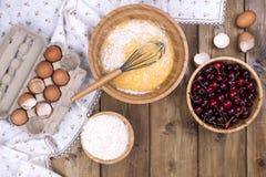 Przygotowanie domowej roboty słodcy ciasta z wiśniami Jajka, mąka i jagody na drewnianym tle, Mieszkanie nieatutowy, kopii przest zdjęcia stock