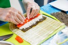 Przygotowanie suszi rolka w restauraci, zamyka up na szef kuchni rękach obraz stock