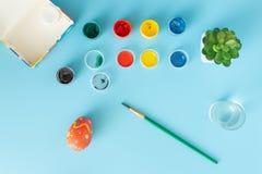 Przygotowywać dla Wielkanocnych multicolor farb i Ręcznie robiony barwionego jajka obok muśnięcia na błękitnym bacground wielkano zdjęcia royalty free