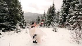 Przygotowywa przędzalnianego szczęśliwego panny młodej mienia, przędzalnictwa podczas opad śniegu i ona w jego rękach w śnieg pog zdjęcie wideo