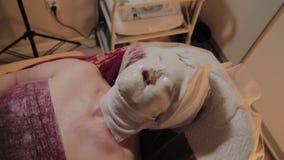 Przygotowywająca starsza kobieta jest ubranym maskę na procedurze w piękno salonie zbiory wideo