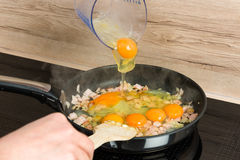 Przygotowywający dla śniadania: gotować rozdrapanych jajka w nowożytnej kuchni Zdjęcia Stock