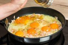 Przygotowywający dla śniadania: gotować rozdrapanych jajka w nowożytnej kuchni Zdjęcia Royalty Free