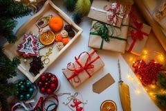 Przygotowywający dla wakacji, zawijający prezenty w Kraft papierze, etykietki dla podpisu, otaczać Bożenarodzeniowymi błahostkami obrazy royalty free