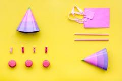 Przyjęć urodzinowych akcesoria Partyjny kapelusz, cukierki, papierowa torba dla prezenta na żółtym tło odgórnego widoku kopii egz Obraz Royalty Free