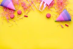 Przyjęć urodzinowych akcesoria Partyjny kapelusz, cukierki, papierowa torba dla prezenta na żółtym tło odgórnego widoku kopii egz Obraz Stock