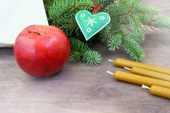 Przyjęcia gwiazdkowego przygotowania tło z czerwonym jabłkiem, naturalne wosk świeczki blisko świeżych naturalnych gałąź choinki  fotografia stock