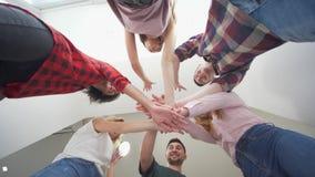 Przyjaźń i związek, dolny widok uśmiechnięci ludzie stawiać ręk wpólnie i wtedy podnoszący zdjęcie wideo