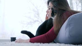 Przyjaźń zwierzęta z ludźmi, ładna dziewczyna obejmuje kota na tle wielki okno zbiory