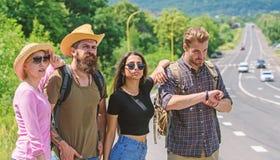 Przyjaciół autostopowicze patrzeje dla transportu słonecznego dnia Zaczyna wielką przygodę w twój życiu z hitchhiking firma fotografia stock