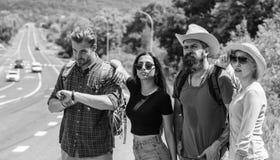 Przyjaciół autostopowicze patrzeje dla transportu słonecznego dnia Zaczyna wielką przygodę w twój życiu z hitchhiking firma fotografia royalty free