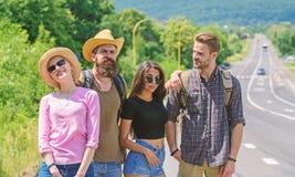 Przyjaciół autostopowicze patrzeje dla transportu słonecznego dnia Firma przyjaciół podróżnicy hitchhiking przy krawędzi drogi na fotografia royalty free