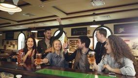 Przyjaciół fan piłki nożnej rozweselają dalej w sporta barze ogląda znacząco dopasowanie i ma zabawę w końcówce Są zbiory