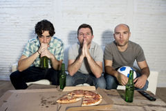 Przyjaciół zagorzali fan piłki nożnej ogląda tv dopasowywają z piwnymi butelkami i pizzy cierpienia stresem Obraz Stock