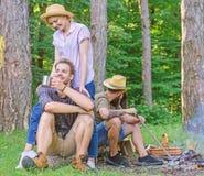 Przyjaciela relaksujący pobliski ognisko po dnia wycieczkuje natury tło Firma przyjaciele cieszą się relaksujący wpólnie las zdjęcia royalty free
