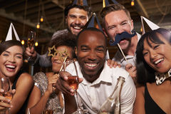 Przyjaciele świętuje nowego roku przy barem w partyjnych kapeluszach, zamykają up Zdjęcie Stock