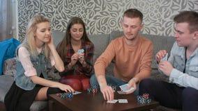 Przyjaciele bawić się partię pokeru, rozdający zakładać się i karty obraz royalty free