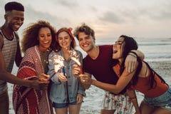Przyjaciele bawi si? na pla?y z sparklers zdjęcia stock
