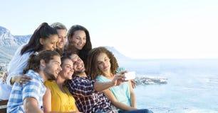 Przyjaciele bierze grupową fotografię przeciw rozmytej linii brzegowej fotografia royalty free