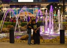 Przyjaciele bierze selfie na magenta iluminated wodną fontannę w zawody międzynarodowi przejażdżki terenie zdjęcie stock