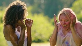 Przyjaciele bryzga wodę na dwa excited młode kobiety zakrywać w koloru proszku zdjęcie wideo