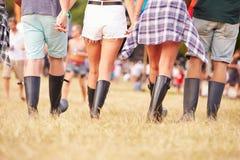Przyjaciele chodzi wpólnie przy festiwalu muzyki miejscem, tylny widok Fotografia Stock