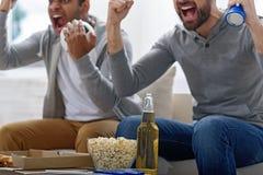 Przyjaciele cieszy się piłkę nożną w TV Zdjęcia Royalty Free