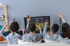 Przyjaciele cieszy się piłkę nożną w TV zdjęcie royalty free