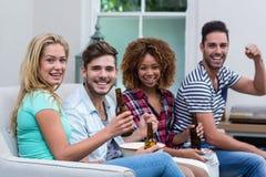 Przyjaciele cieszy się piwo podczas gdy oglądający mecz piłkarskiego w domu Fotografia Royalty Free