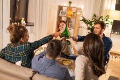 Przyjaciele clinking napoje w wiecz?r w domu obraz stock