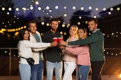 Przyjaciele clinking partyjne filiżanki na dachu przy nocą obrazy royalty free