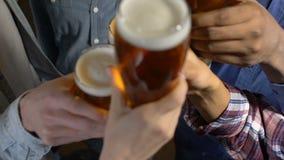 Przyjaciele clinking piwnych szkła, świętuje ulubionego sport drużyny zwycięstwo w pubie zbiory wideo