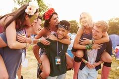 Przyjaciele daje piggybacks przez festiwalu muzyki campsite Zdjęcia Stock