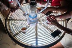 Przyjaciele dymią nargile i piją alkohol przy nocy kawiarnią obraz stock