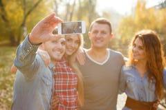 Przyjaciele fotografują z smartphone w parku obrazy stock