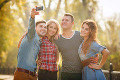Przyjaciele fotografują z smartphone w parku zdjęcie stock