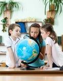 Przyjaciele gapią się przy szkolną kulą ziemską Fotografia Stock