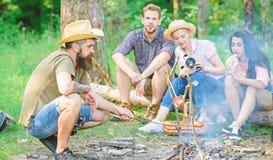 Przyjaciele grupują turystycznego relaksującego pobliskiego ognisko Obsługuje prażak kiełbasę podczas gdy przyjaciele mówją częśc zdjęcie stock
