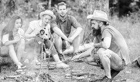 Przyjaciele grupują turystycznego relaksującego pobliskiego ognisko Obsługuje prażak kiełbasę podczas gdy przyjaciele mówją częśc fotografia royalty free