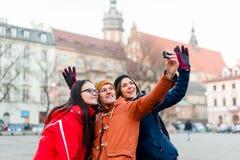 Przyjaciele halsuje selfies z noszoną kamerą w turystycznym mieście Zdjęcie Stock