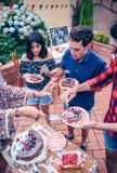 Przyjaciele je tort i ma zabawę w przyjęciu obrazy royalty free
