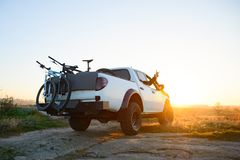 Przyjaciele Jedzie Pickup Offroad ciężarówkę w górach z rowerami w ciele przy zmierzchem Przygody i podróży pojęcie zdjęcia stock