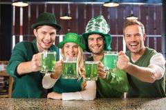 Przyjaciele jest ubranym St Patricks dzień kojarzącego odziewają wznosić toast zdjęcie stock