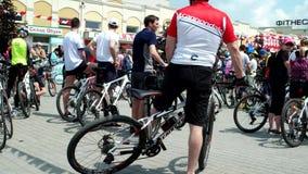 Przyjaciele komunikują cyklistów na tle mnóstwo ludzie na bicyklach, mężczyzna przygotowywają dla rower przejażdżki zbiory