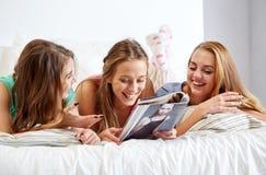 Przyjaciele lub nastoletnie dziewczyny czyta magazyn w domu Zdjęcia Royalty Free