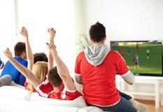 Przyjaciele lub piłek nożnych fan ogląda grę na tv w domu Fotografia Stock