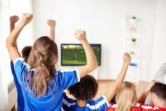 Przyjaciele lub piłek nożnych fan ogląda grę na tv w domu Obrazy Stock