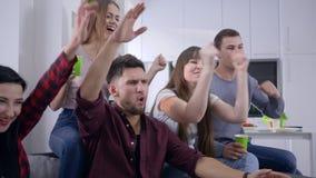 Przyjaciele odpoczywają w domu, szczęśliwi faceci z dziewczynami cieszą się dopatrywanie telewizję i energicznie dyskutują film p zbiory