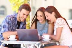 Przyjaciele ogląda środek zawartość na laptopie w barze zdjęcie stock